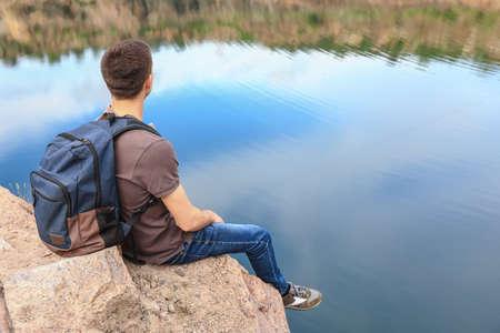 Male tourist near mountain lake