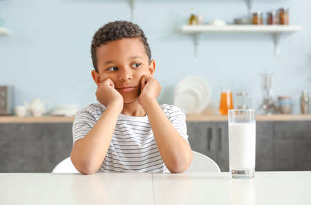Cute African-American boy with glass of milk at table