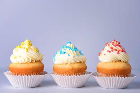 Tasty Birthday cupcakes on gray background