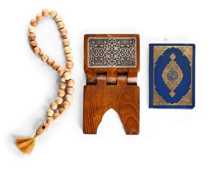 Muslim beads, rehal and Koran on white background