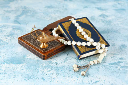 Koran, rehal, lamp and Muslim beads on color background