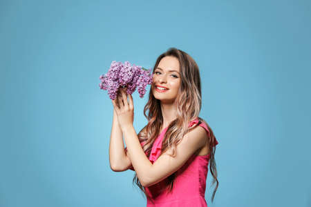 Beautiful young woman with bouquet of lilac flowers on color background Stock Photo