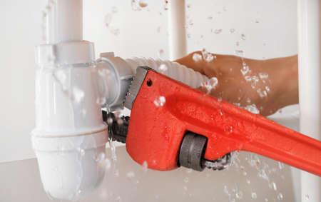 Plumber repairing pipes of kitchen sink, closeup