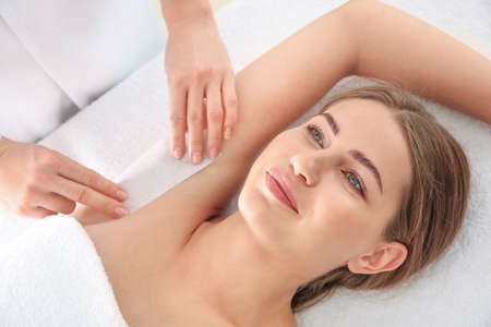 Young woman undergoing armpits epilation in beauty salon