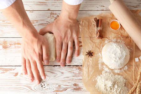 Man kneading dough on kitchen table, top view