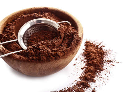 Bowl with cocoa powder and sieve on white background