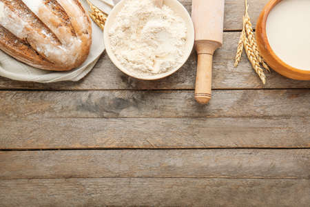 Flour with bread, milk and rolling pin on wooden background