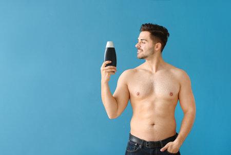 Handsome man with bottle of shampoo on color background Banque d'images