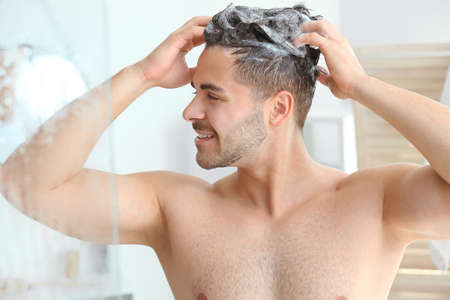 Handsome man washing hair in bathroom