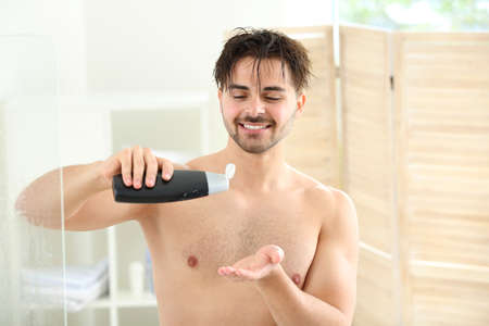 Handsome man with bottle of shampoo taking shower at home