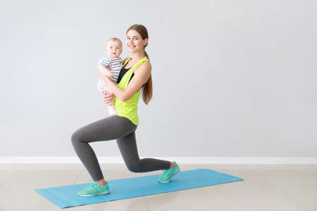 Mother training with cute little baby indoors Standard-Bild