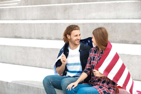 Happy young couple with USA flag outdoors. Independence Day celebration