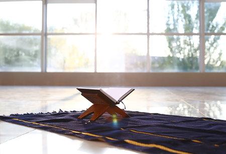 Rehal with open Koran on Muslim prayer mat indoors
