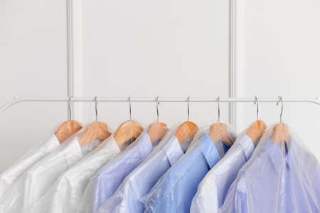 Rack with clothes after dry-cleaning near white wall Foto de archivo