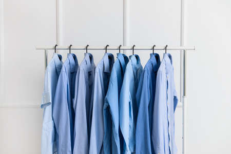 Rack with clothes after dry-cleaning near white wall