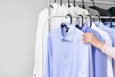 Woman hanging clothes on rack after dry-cleaning