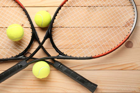 Tennis rackets and balls on wooden background