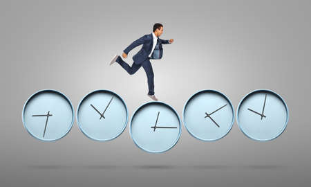 Running African-American businessman with clocks on gray background. Deadline concept