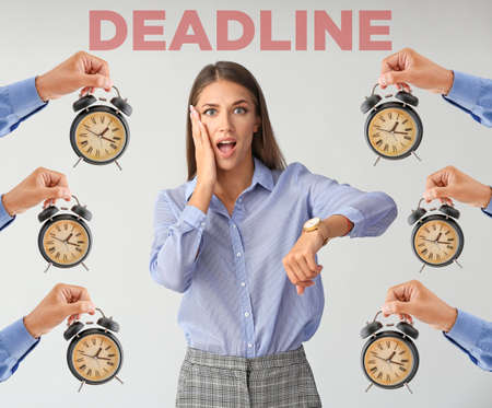 Shocked young businesswoman and hands with alarm clocks on gray background. Deadline concept