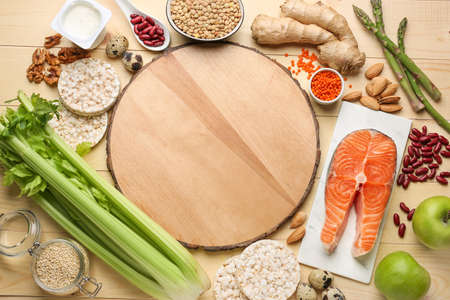Different healthy food with board on wooden table
