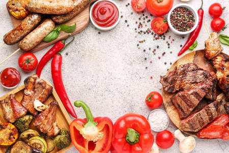 Frame made of tasty grilled meat with sausages and vegetables on gray background
