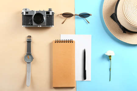 Photo camera, sunglasses, notebook, watch and hat on color background Standard-Bild