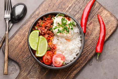 Bowl with tasty chili con carne and rice on table