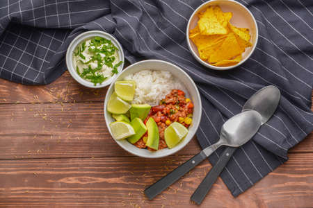 Bowl with tasty chili con carne and rice on wooden table