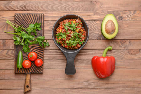 Tasty chili con carne with fresh vegetables on wooden table