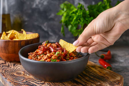 Woman eating tasty chili con carne with nachos