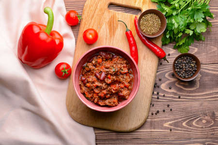 Bowl with tasty chili con carne on wooden background