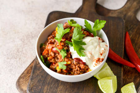 Bowl with tasty chili con carne on table