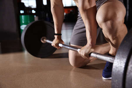 Sporty young man training with barbell in gym
