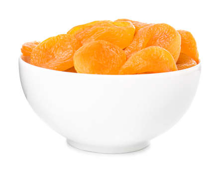 Bowl with tasty dried apricots on white background