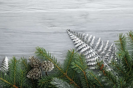 Fir tree branches with cones on wooden background
