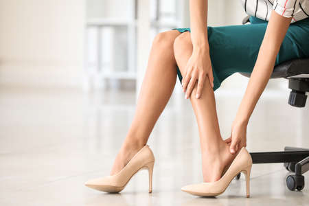 Young woman feeling ache because of wearing high heels in office