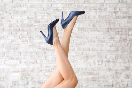 Legs of young woman in high-heeled shoes on brick background