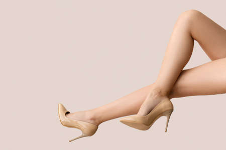 Legs of young woman in high-heeled shoes on light background
