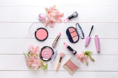 Set of makeup cosmetics with flowers on white wooden background Standard-Bild