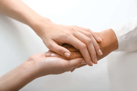 Hands of young and elderly woman on white background. Concept of support Stock Photo