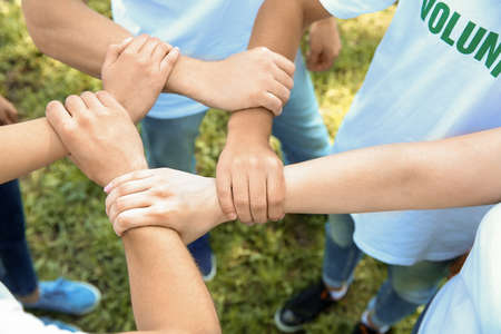Team of volunteers holding hands together outdoors Standard-Bild