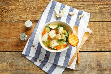 Bowl of tasty soup on wooden table Foto de archivo