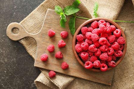 Plate with fresh raspberries on dark table