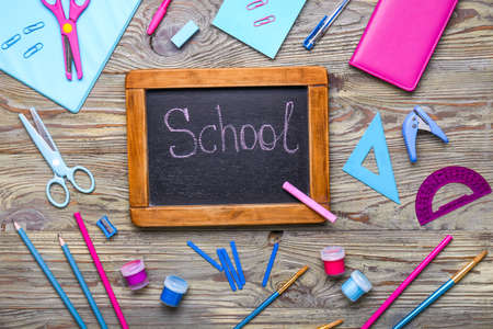 Set of school supplies with chalkboard on wooden background