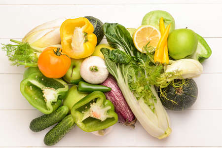 Assortment of fresh vegetables and fruits on white wooden background