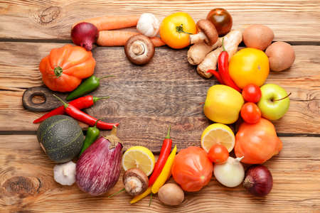 Board with assortment of fresh vegetables and fruits on wooden background