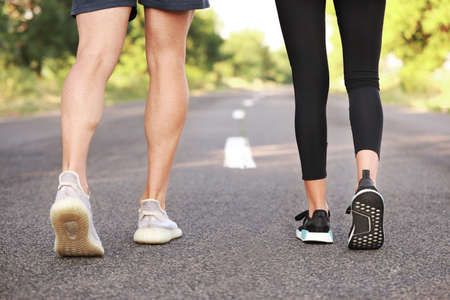 Legs of sporty young couple running outdoors