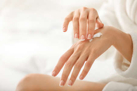 Young woman applying natural cream onto skin at home Stockfoto