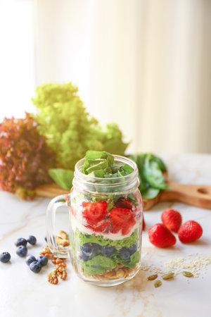Mason jar with fresh tasty salad on table