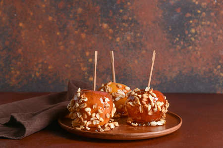 Plate with tasty candy apples on table
